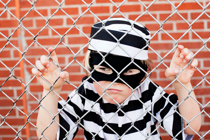 Child wearing inmate costume.